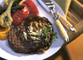 Grilled Rib Eye Steak with Canadian Cheddar and Roasted Onion Sauce